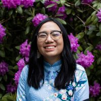 woman in blue floral shirt and glasses smiles brightly in front of plant with purple flowers